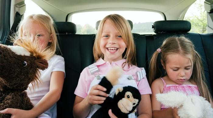 Three kids have fun in the car on a road trip
