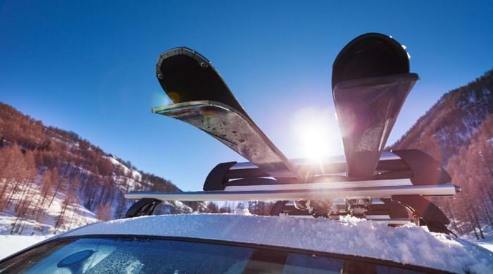 Skis strapped up to a roof rack, ready to hit the slopes.